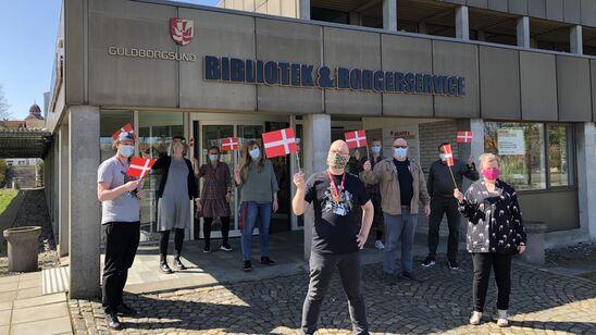 personale med flag uden for biblioteket