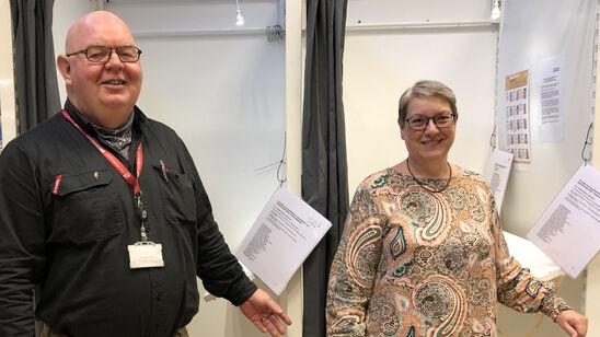 En mand og en kvinde foran stemmebokse