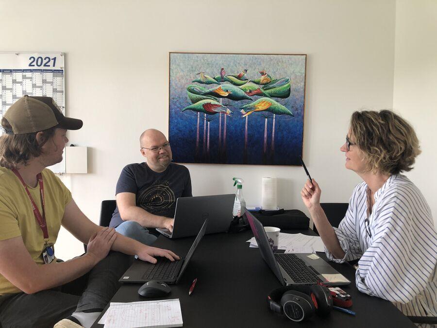 Tre mennesker, der holder møde og arbejder