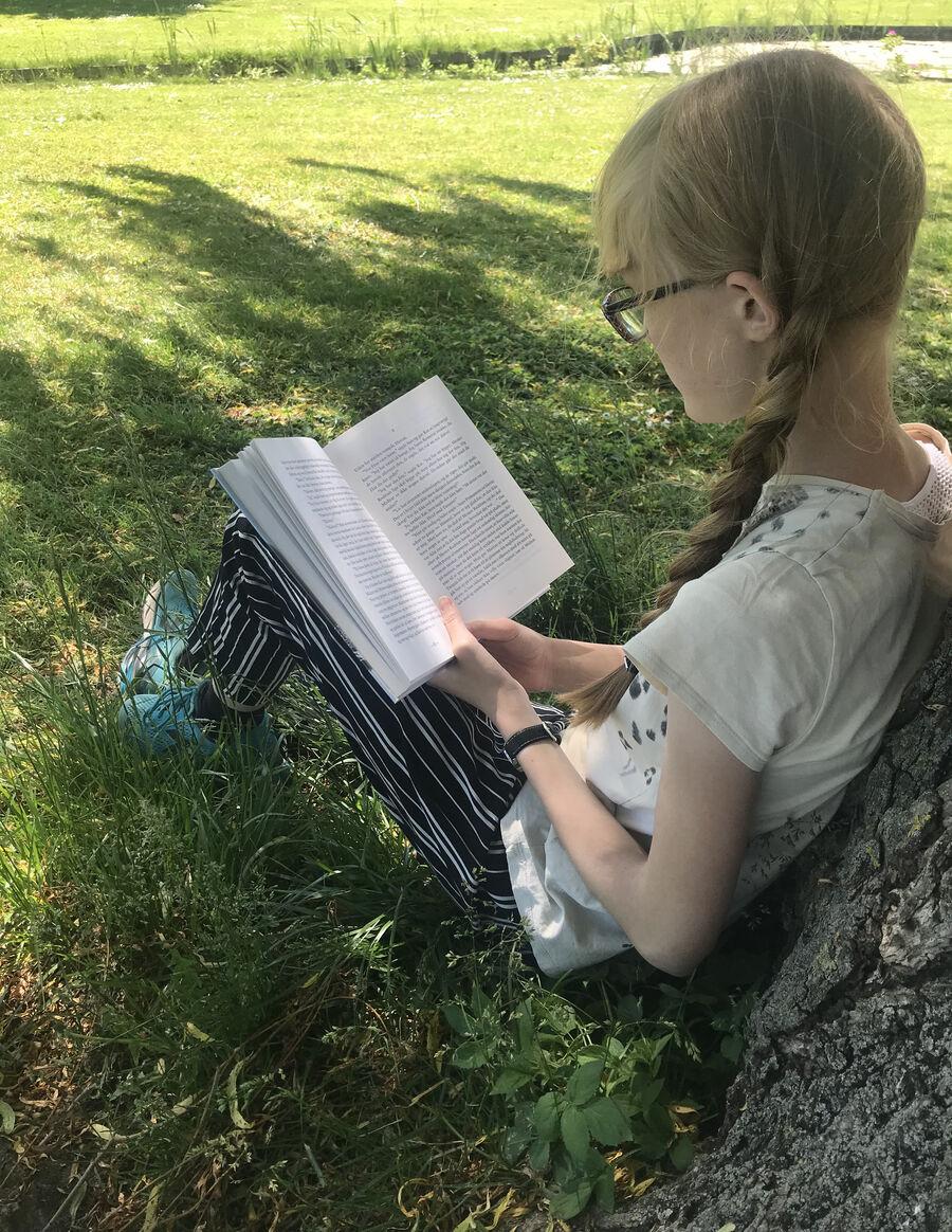 Pige der læser siddende op ad et træ