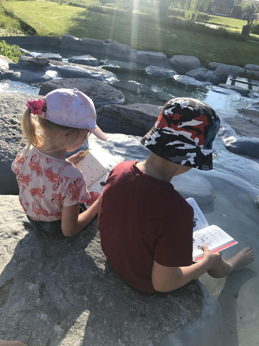 En pige og en dreng der læser med fødderne i et bassin