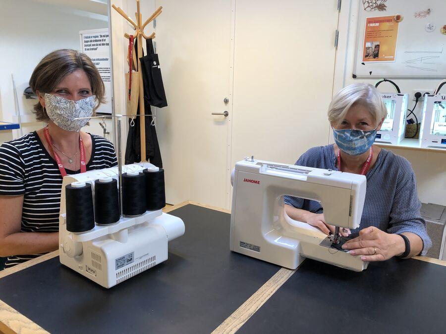 To kvinder med mundbind foran symaskiner